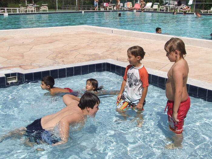 Kids swim in a pool at the Oak Village Sports Complex